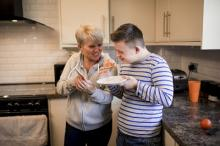 Two people pictured in kitchen promoting Warm Homes Hub